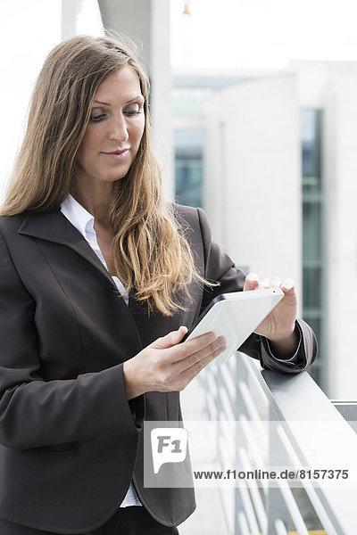 Geschäftsfrau mit digitalem Tablett  lächelnd