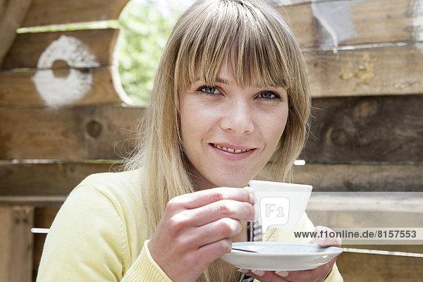 Deutschland  Nordrhein-Westfalen  Köln  Porträt einer jungen Frau im Becher  lächelnd
