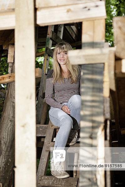 Deutschland  Nordrhein-Westfalen  Köln  Junge Frau auf der Treppe am Spielplatz sitzend  lächelnd