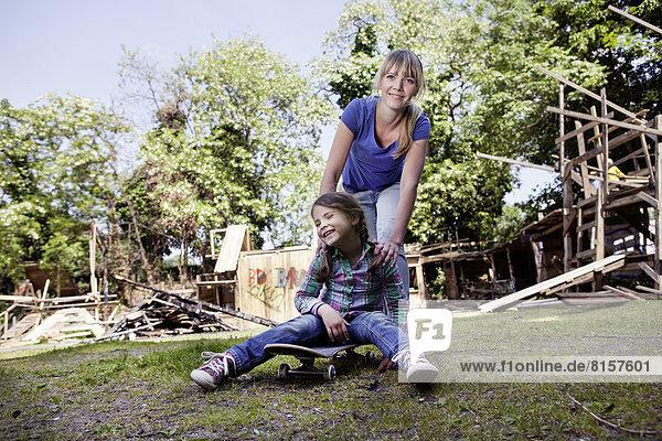 Deutschland  Nordrhein-Westfalen  Köln  Mutter und Tochter spielen mit Skateboard  lachend