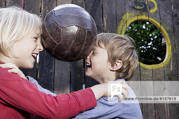 Deutschland  Nordrhein-Westfalen  Köln  Jungen spielen mit Ball im Spielplatz  lächeln