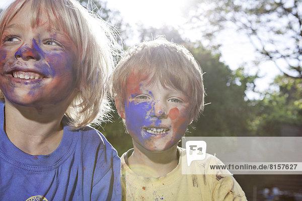 Deutschland  Nordrhein-Westfalen  Köln  Jungen spielen mit Farben auf dem Spielplatz  lächeln