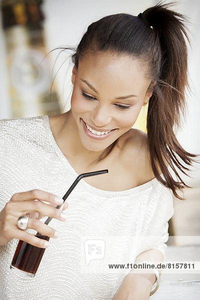 Deutschland  Junge Frau hält ein Glas Koks  lächelnd