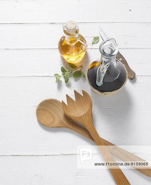 Salatbesteck mit Öl und Essig auf weißem Hintergrund  Nahaufnahme