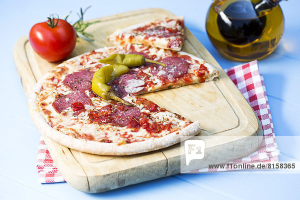 Pizza with salami on chopping board  close up