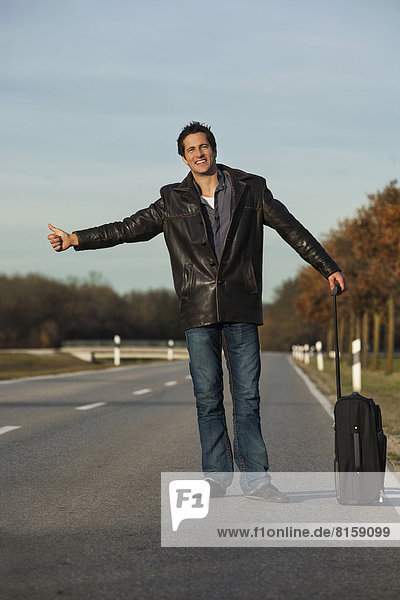 Deutschland  Bayern München  Mid adult man hitchiking on road