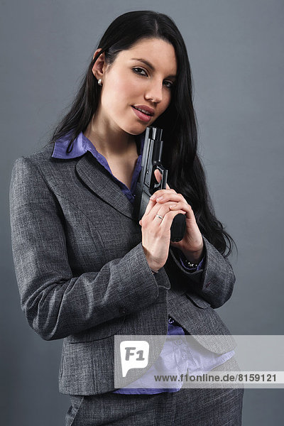 Young woman wearing holding gun  portrait  close up