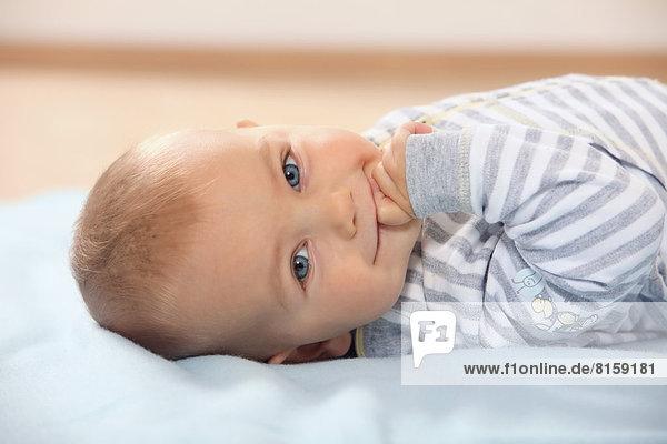 Porträt des Jungen auf dem Handtuch liegend  lächelnd