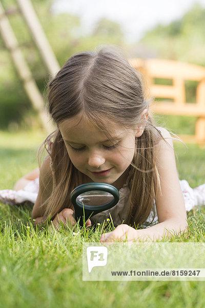Girl looking through magnifying glass in graden