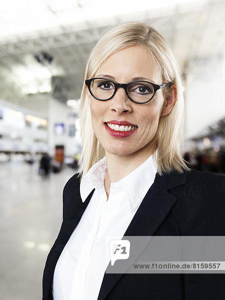 Portrait der Geschäftsfrau am Flughafen  lächelnd  Mund