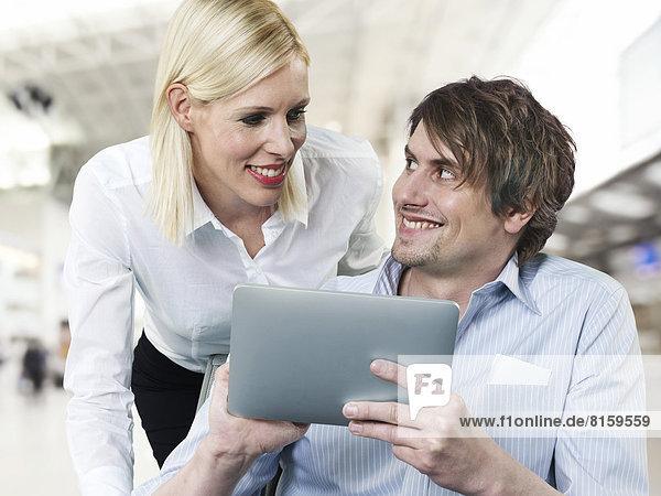 Geschäftsmann und Geschäftsfrau mit digitalem Tablett  lächelnd