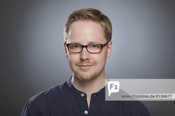 Porträt eines jungen Mannes vor grauem Hintergrund  Nahaufnahme