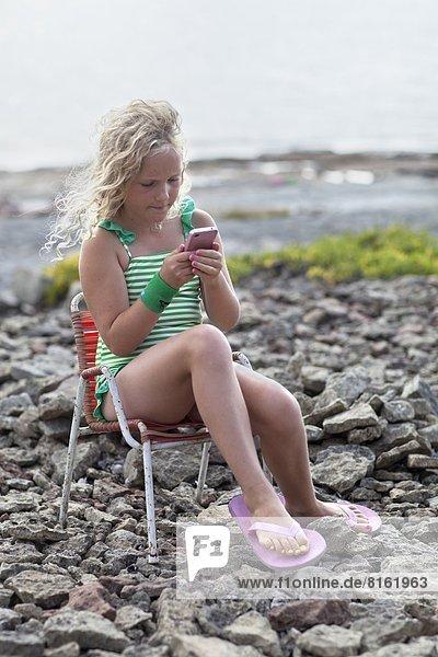 Handy sitzend Strand Mädchen