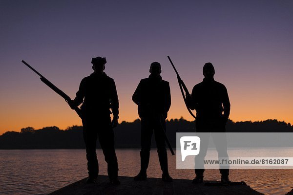 Silhouette of three hunters on jetty at sunset