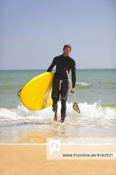 Happy man walking with paddleboard