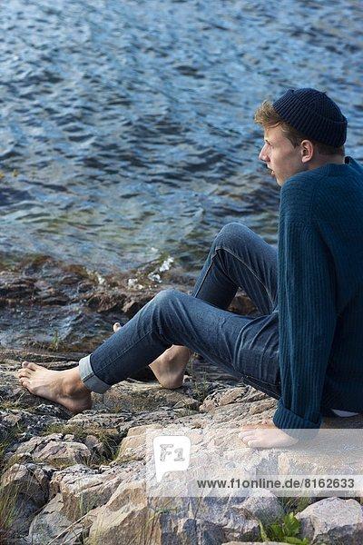 Felsbrocken  sitzend  Wasser  Jugendlicher  sehen  Junge - Person