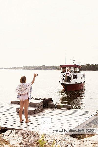 Girl waving to man on ferry