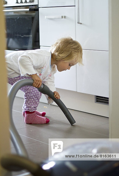 Girl cleaning kitchen with hoover