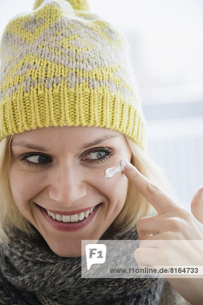 Portrait of smiling woman applying face cream