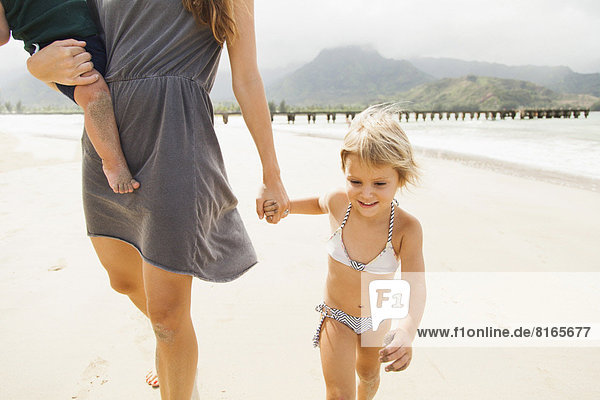 Mother walking with daughters (6-11 months,  2-3) on beach