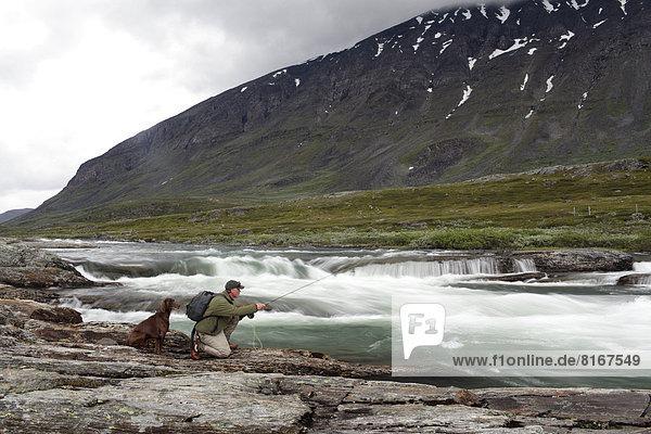 Man fishing wit dog in river