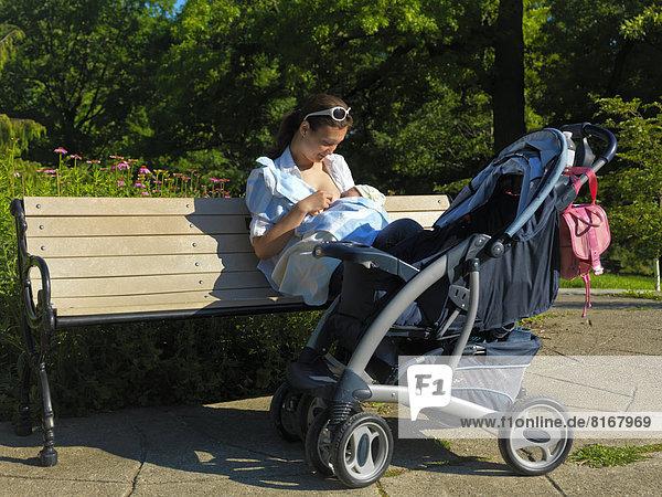 Eine junge Mutter sitzt auf einer Bank und stillt ihr Baby