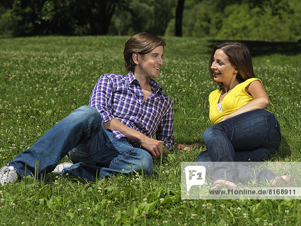 Couple lying on the lawn in a park