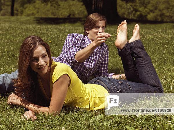 Ein Paar liegt auf dem Rasen in einem Park, der Mann