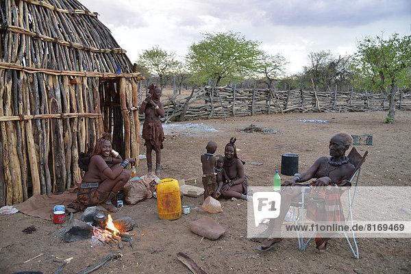 Chief Hikuminue Kapika  der Oberste der namibischen Himba  mit seiner Familie am Feuer in seinem Kral