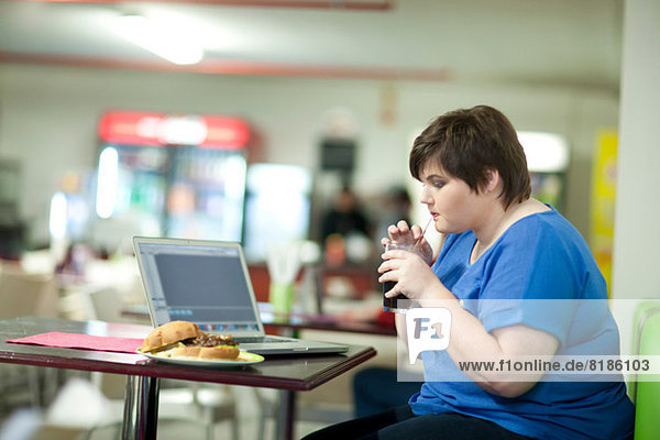 Junge Frau trinkt Koks im Café