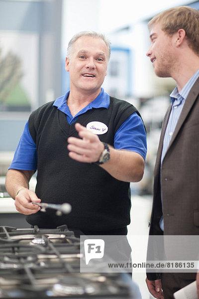 Junger Mann verhandelt mit Verkäufer im Showroom