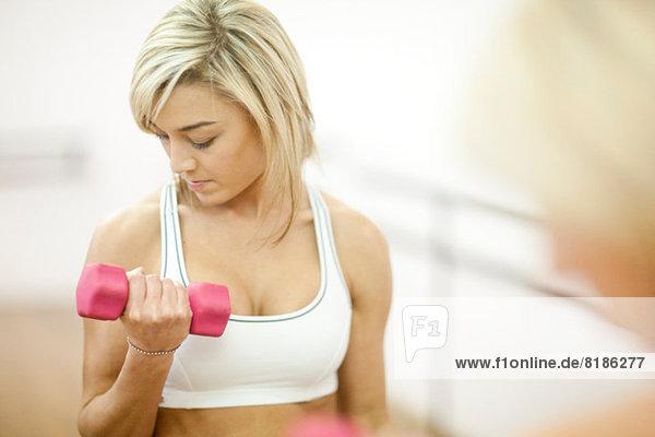 Junge Frau im Fitnesstraining mit Hanteln