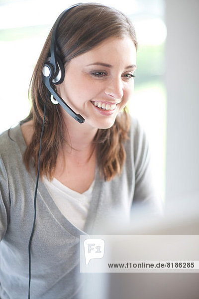 Young woman with headset on computer