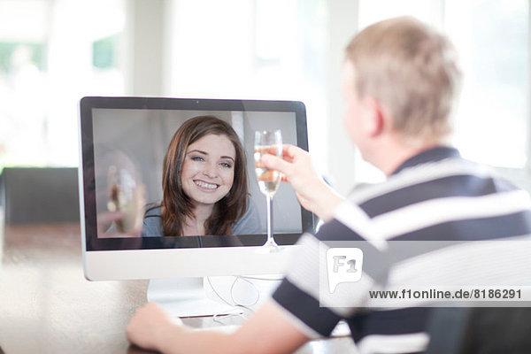 Mann toastet Frau mit Videogespräch