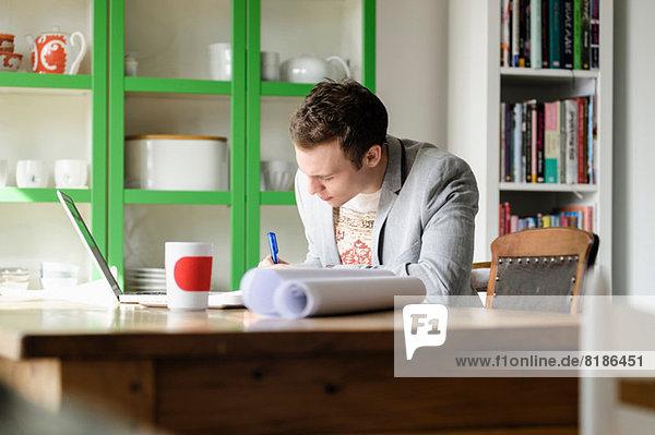Mann schreibt am Schreibtisch