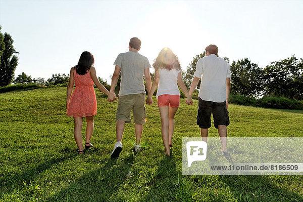 Gruppe junger Erwachsener beim Gehen und Händchenhalten