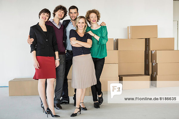 Businesspeople standing in front of pile of cardboard boxes