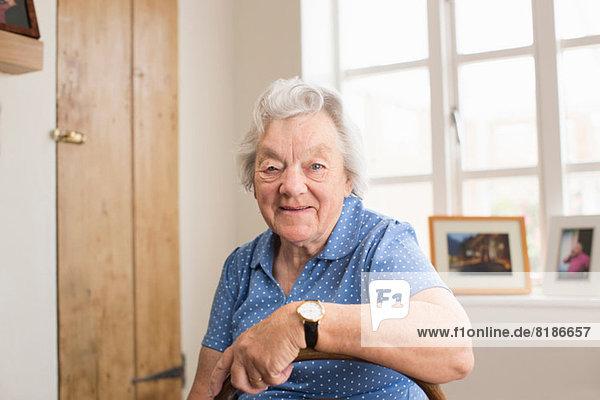 Seniorin im Zimmer sitzend