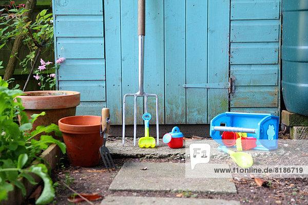 Gartengeräte  Töpfe und Spielzeug außerhalb des Schuppens