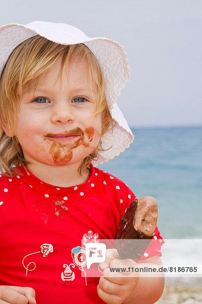Baby Mädchen isst Eis am Strand