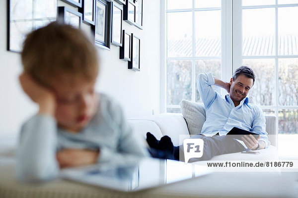 Father and son sitting on sofa using digital tablets