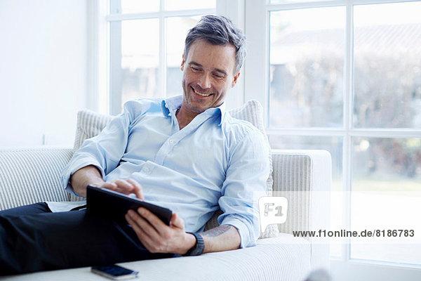 Mann entspannt auf dem Sofa mit digitalem Tablett