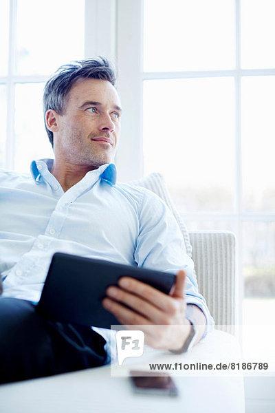 Mann auf Sofa sitzend mit digitalem Tablett