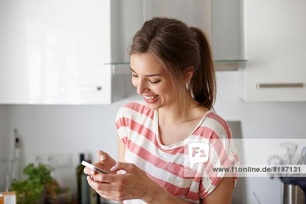 Frau lächelt und benutzt Handy