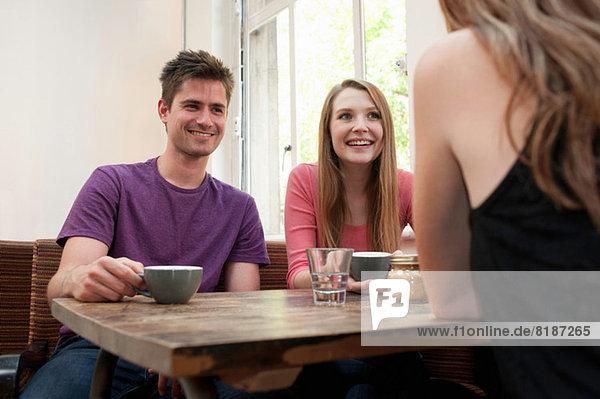 Gruppe von Freunden beim Plaudern im Café