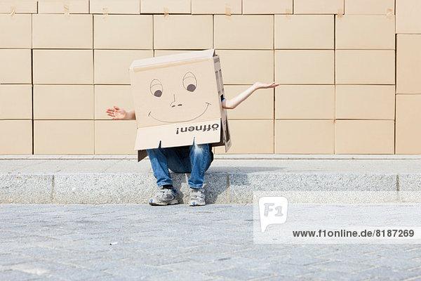 Mann mit einer Pappschachtel  die seinen Kopf bedeckt.