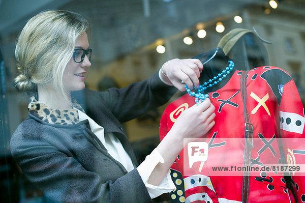 Frau legt Halskette auf Ladenpuppe