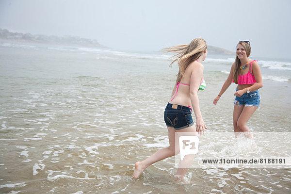 Junge Frauen spielen bei Flut am Strand