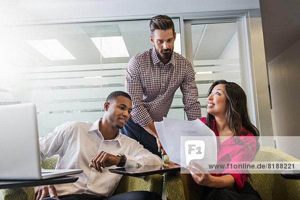 Junge Geschäftskollegen beim Betrachten von Dokumenten im Meeting
