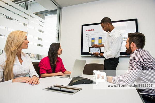Junge Geschäftskollegen beim Blick auf den digitalen Tisch im Besprechungsraum